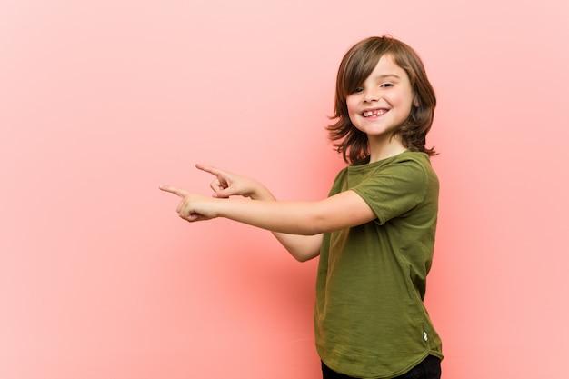 Garotinho animado apontando com o dedo indicador fora.