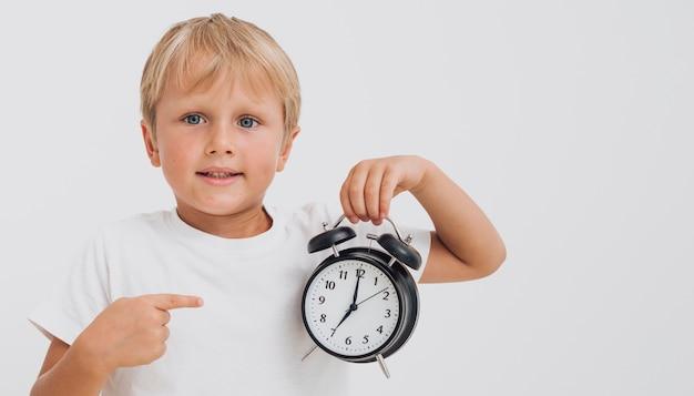 Garotinho, apontando para um relógio