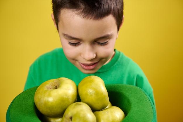 Garotinho aprecia o cheiro de maçãs verdes em um boné irlandês verde