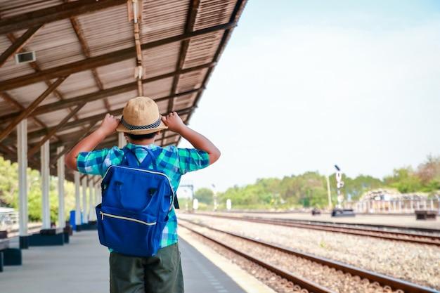 Garotinho asiático carregando uma mochila azul em pé esperando o trem ir para a escola