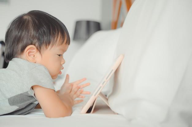 Garotinho asiático deitado na cama assistindo a uma história no tablet touchscreen