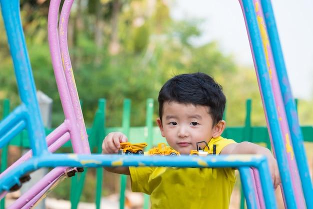 Garotinho asiático jogando slide no parque infantil