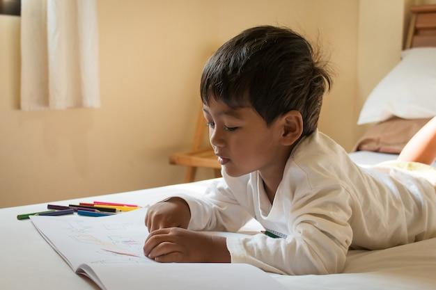 Garotinho asiático pintar no livro branco na sala