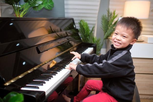 Garotinho asiático sorridente feliz e fofo tocando piano na sala de estar