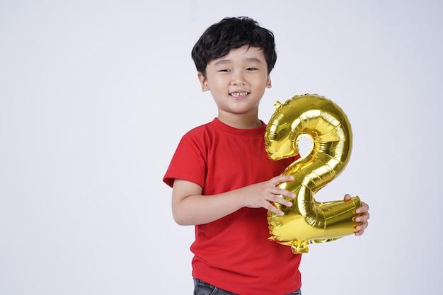 Garotinho asiático sorrindo feliz com um balão de papel alumínio, isolado no fundo branco