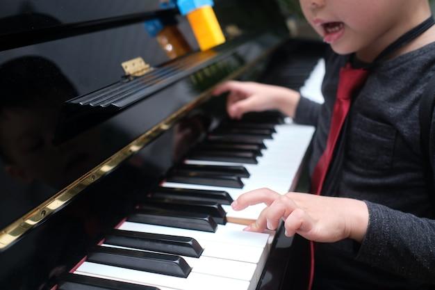 Garotinho asiático tocando piano na sala de estar de casa
