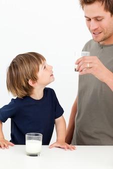 Garotinho assistindo seu pai bebendo leite