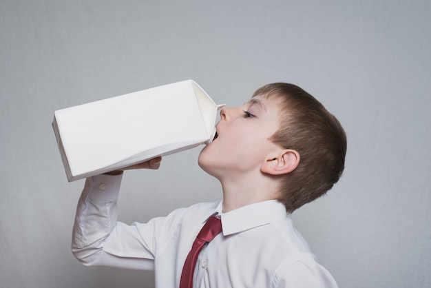 Garotinho bebe de um grande pacote branco. camisa branca e gravata vermelha