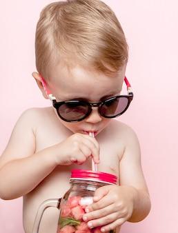 Garotinho, bebendo limonada fresca com um pedaço de melancia e gelo em rosa.