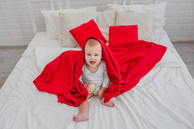 Garotinho bonito em um macacão branco está sentado em uma cama com um cobertor vermelho