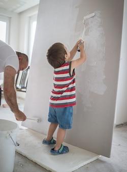 Garotinho bonito pintura em uma parede