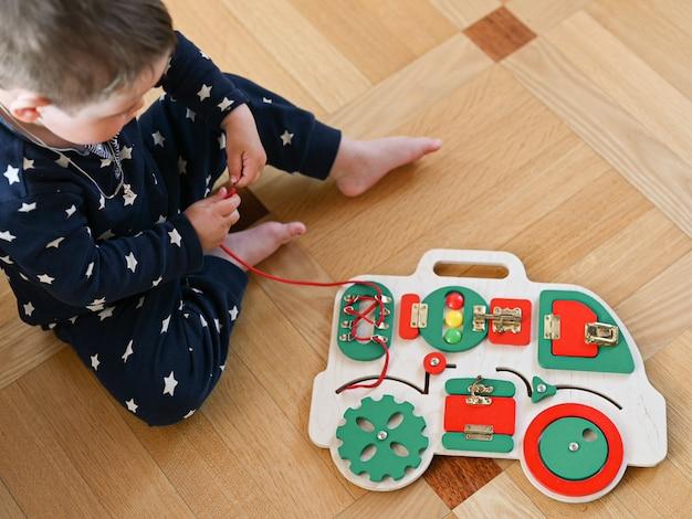 Garotinho brinca com um brinquedo de desenvolvimento