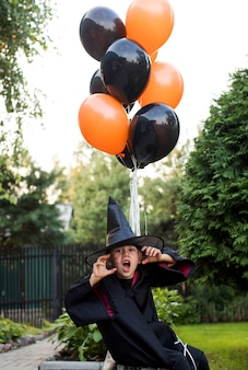 Garotinho brincalhão com fantasia de carnaval de mago ameaça celebrar o dia das bruxas no quintal