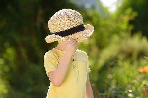 Garotinho brincando, cobre o rosto com um chapéu de palha.