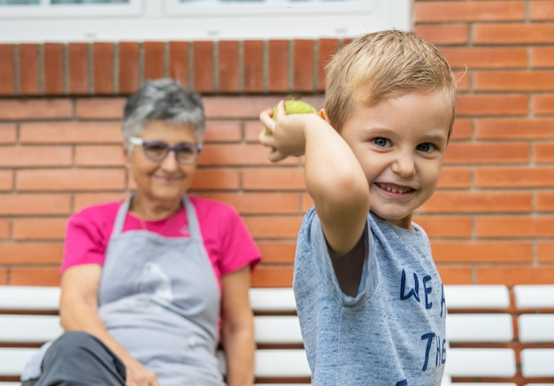 Garotinho brincando com a bola enquanto sua avó está olhando para ele
