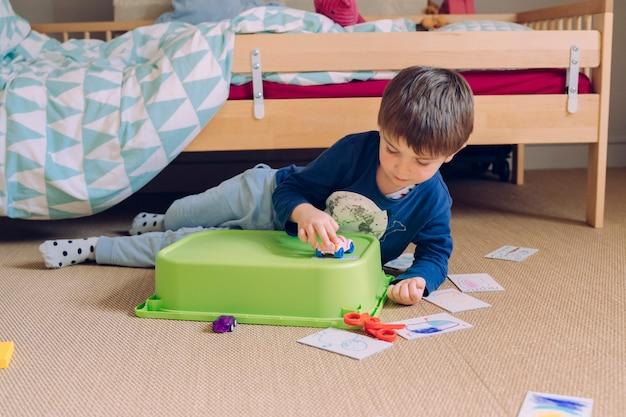 Garotinho brincando com carros e jogos para crianças pequenas