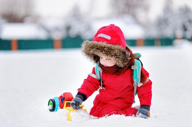 Garotinho brincando com o brinquedo do carro brilhante e neve fresca em um dia de inverno