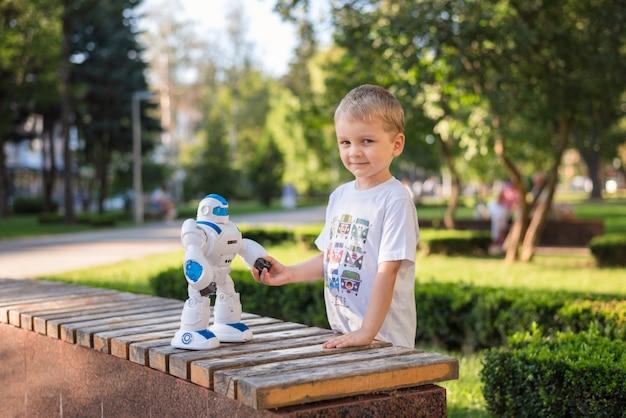 Garotinho brincando lá fora com um robô
