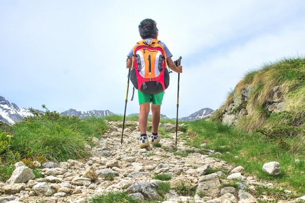 Garotinho caminha na trilha de montanha durante uma excursão. com a mochila