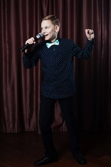 Garotinho cantando no microfone.
