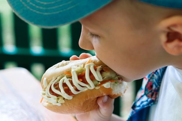 Garotinho caucasiano comendo hambúrguer