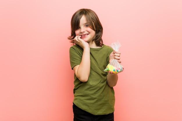 Garotinho caucasiano segurando doces mordendo as unhas, nervoso e muito ansioso.