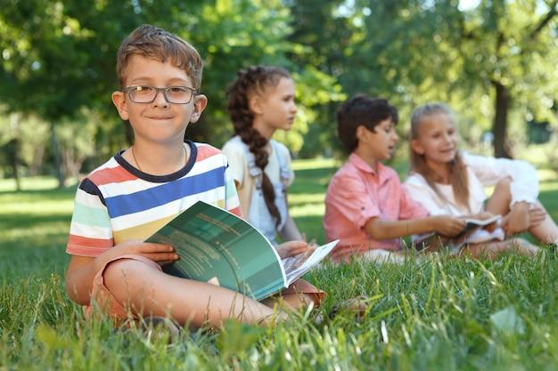 Garotinho charmoso sorrindo para a frente, enquanto lê um livro, sentado na grama