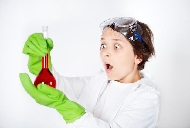 Garotinho chocado com vidraria de laboratório