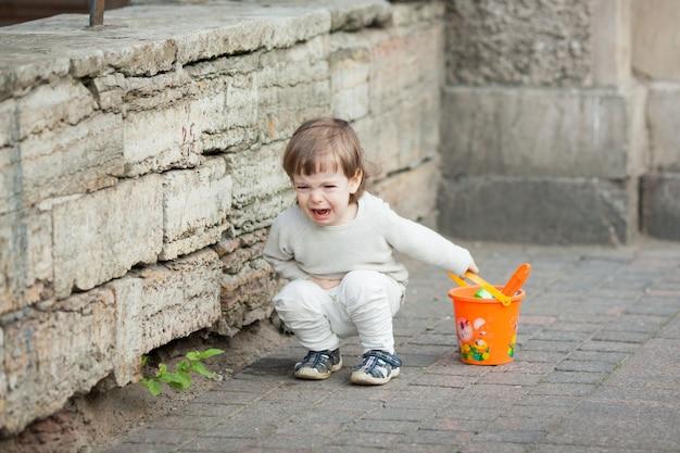 Garotinho chorando em pé na rua.