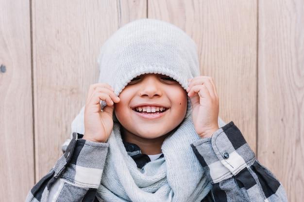 Garotinho, cobrindo os olhos com boné de inverno