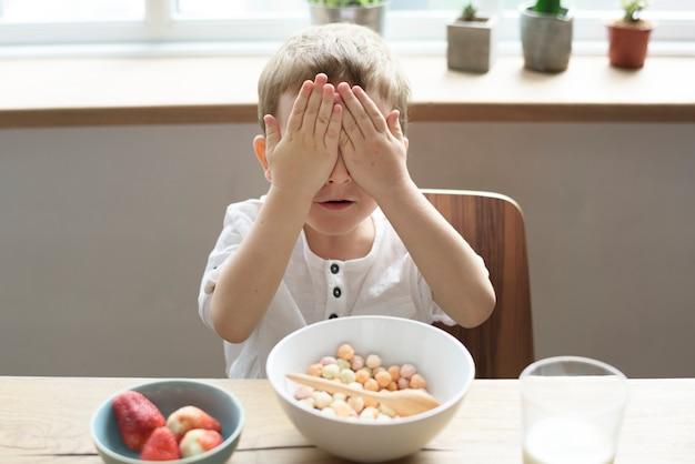 Garotinho, cobrindo os olhos enquanto tomando café da manhã