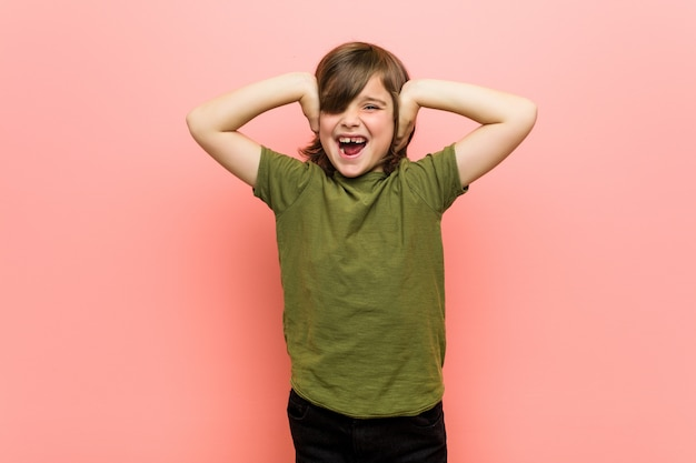 Garotinho, cobrindo os ouvidos com as mãos, tentando não ouvir som muito alto.