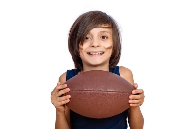 Garotinho com bola de futebol americano.