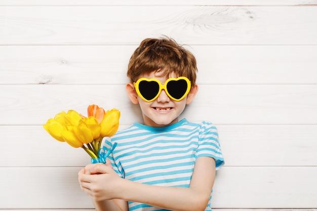 Garotinho com buquê de tulipas. conceito de dia das mães, conceito de férias.