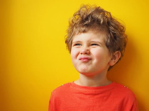 Garotinho com cabelo encaracolado fazendo uma careta