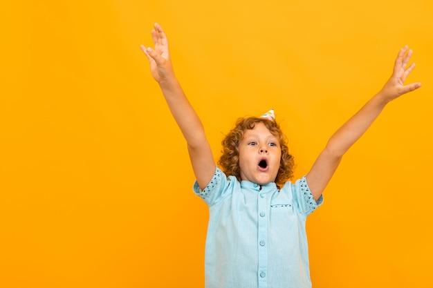 Garotinho com cabelo encaracolado na camisa azul e shorts é feliz porque tem b-dia isolado em fundo amarelo