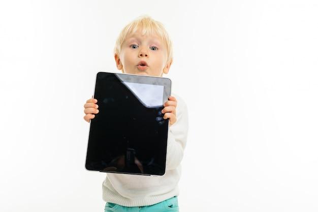 Garotinho com cabelo loiro curto, olhos azuis, aparência bonita, de jaqueta branca, calça azul clara, fica com um tablet e o segura nas mãos