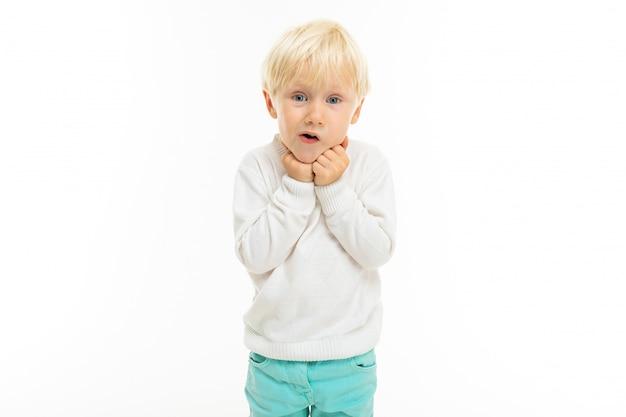 Garotinho com cabelo loiro curto, olhos azuis, aparência fofa, jaqueta branca, calça azul clara, fica de pé e fica surpreso