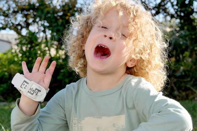 Garotinho com cabelo loiro e encaracolado, fazendo caretas