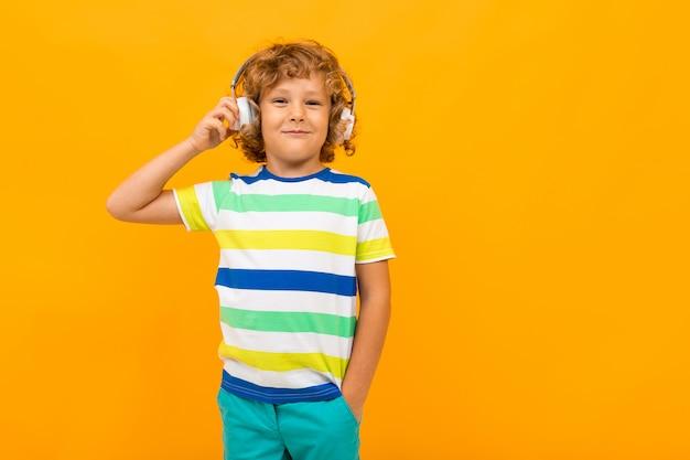 Garotinho com cabelos cacheados em t-shirt colorida e shorts ouve música com fones de ouvido grandes isolados em fundo amarelo