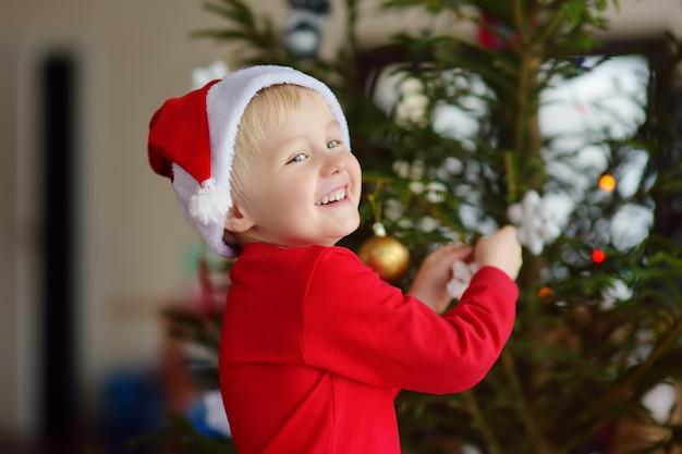Garotinho com chapéu de papai noel pronto para comemorar o natal. bonita criança decorando a árvore de natal com brinquedo de vidro