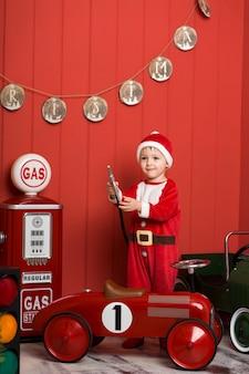 Garotinho com fantasia de papai noel monta um carro de brinquedo vermelho.