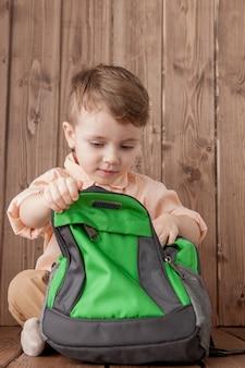 Garotinho com grande saco de escola em fundo de madeira