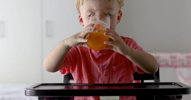 Garotinho com laranjas e suco. menino feliz bebendo suco de laranja em casa