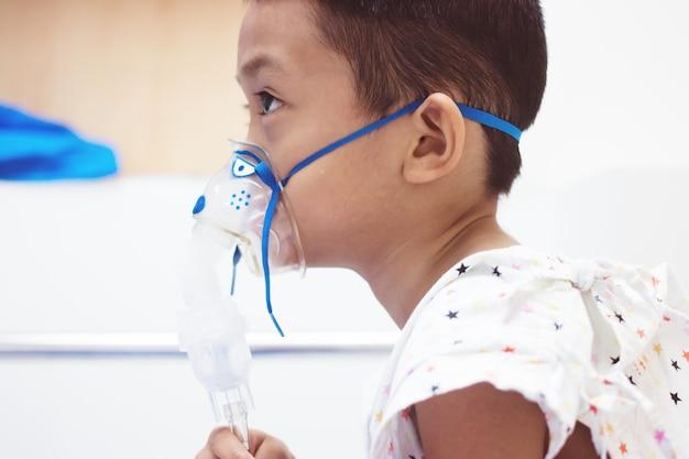 Garotinho com máscara de inalador no hospital