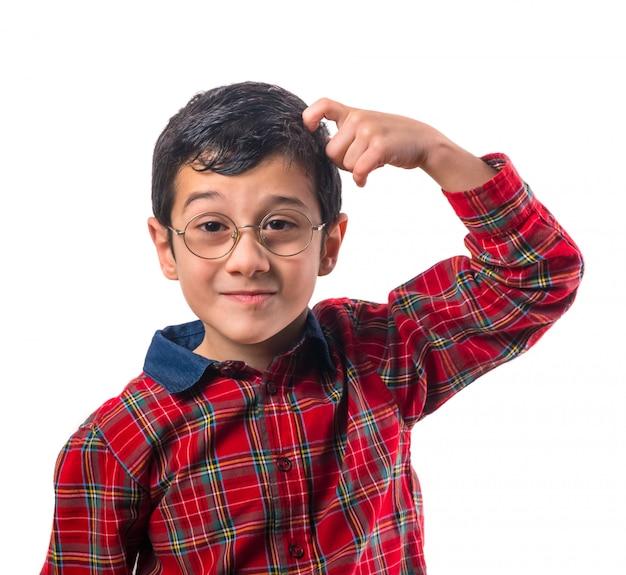 Garotinho com óculos coça a cabeça