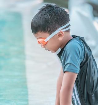 Garotinho com óculos de natação e maiô está jogando na piscina