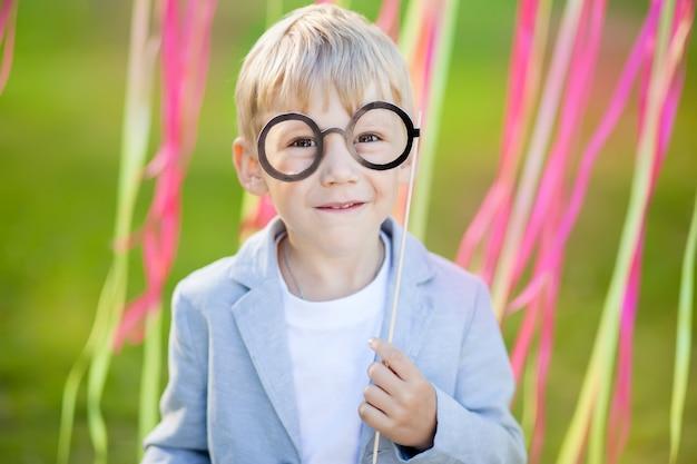 Garotinho com óculos de papel engraçado