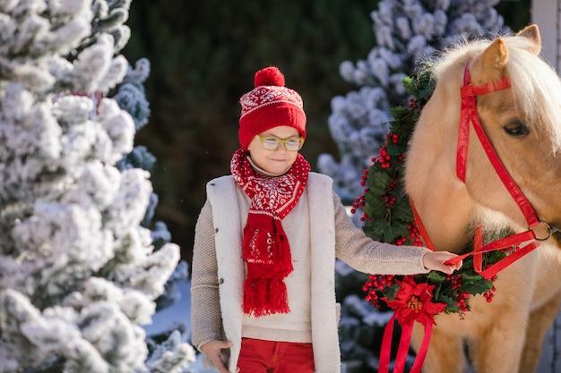 Garotinho com óculos detém seu pônei adorável com coroa festiva perto da pequena casa de madeira