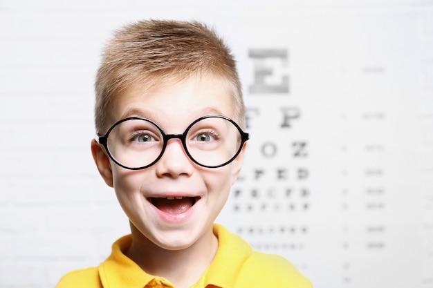 Garotinho com óculos no fundo do gráfico de teste oftálmico
